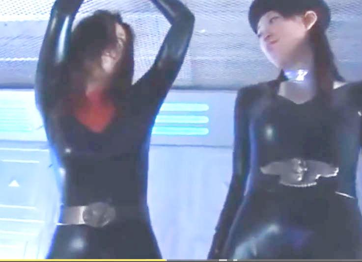 両手拘束状態のラバースーツの美女が拷問を受ける☆敵の女性のえげつない責めに悶絶ぎみ